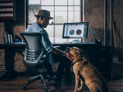 An office dog is hanging around the desk of his master. His master is sitting in a computer chair with his screen on, cradling the office dog's face.